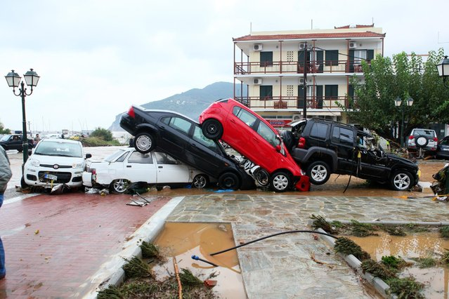 "In this photo taken on Wednesday, September 23, 2015 local residents observe extensive road damage  and cars piled up after floods on the island of Skopelos, central Greece. Authorities in Greece on Thursday, Sept. 24, 2015 have declared a state of emergency following torrential rain on the island of Skopelos, where the 2008 movie ""Mamma Mia!"" was filmed. (Photo by Athina Pouliou/InTime News via AP Photo)"