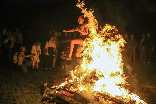 People take part in a traditional mid-summer solstice night celebration (Rasos Festival) at the Open-Air Museum of Lithuania in Rumsiskes, east of Kaunas, Lithuania, on late June 23, 2020. (Photo by Petras Malukas/AFP Photo)