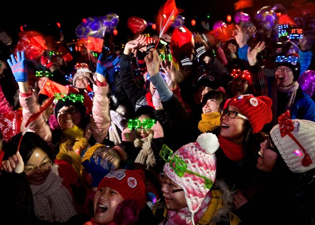 Revelers celebrate the new year during a count-down event at the Summer Palace in Beijing. (Photo by Andy Wong/Associated Press)