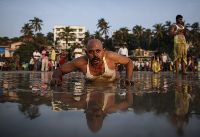 A Hindu devotee lies along the shores of the Arabian Sea as he offers prayers to the Sun god during the Chhat festival in Mumbai October 29, 2014. (Photo by Danish Siddiqui/Reuters)