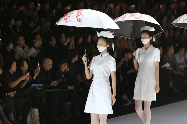 Models wearing masks hold umbrellas as they perform during the TORAY Liu Wei Collection segment at China Fashion Week in Beijing, October 30, 2014. (Photo by Jason Lee/Reuters)