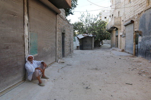 A man sits in front of closed shops in the rebel-held al-Sheikh Said neighbourhood of Aleppo, Syria September 1, 2016. (Photo by Abdalrhman Ismail/Reuters)
