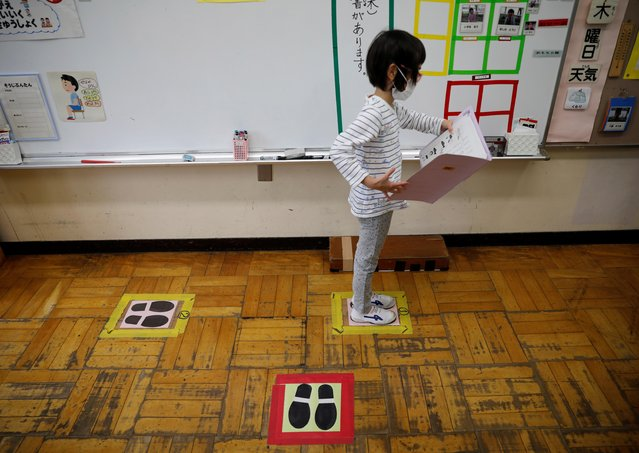 A student wearing a protective face mask stands on a mark for social distancing in a classroom at Takanedai Daisan elementary school in Funabashi, east of Tokyo, Japan, July 16, 2020. (Photo by Kim Kyung-Hoon/Reuters)