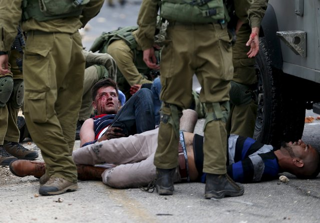 Israeli soldiers detain wounded Palestinian protesters during clashes near the Jewish settlement of Bet El, near the West Bank city of Ramallah, October 7, 2015. (Photo by Mohamad Torokman/Reuters)