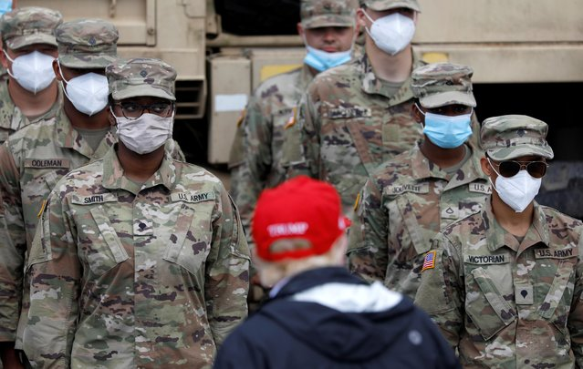 U.S. President Donald Trump looks at members of National Guard wearing masks in formation at Cougar Stadium as he visits nearby areas damaged by Hurricane Laura in Lake Charles, Louisiana, U.S., August 29, 2020. (Photo by Tom Brenner/Reuters)