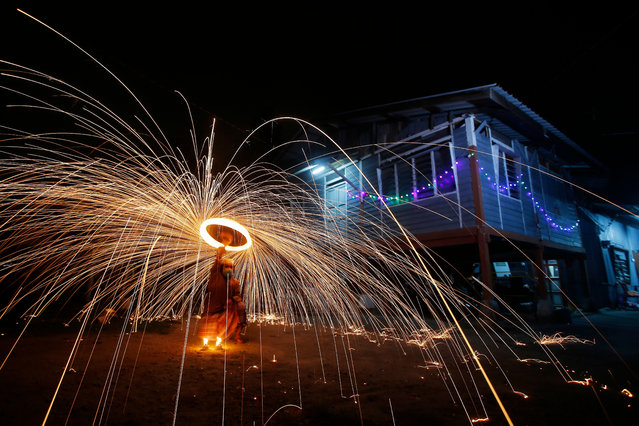 A Malaysian swing around fireworks ahead of Eid al-Fitr celebrations, the religious festival that marks the end of the fasting month of Ramadan, amid the ongoing Coronavirus outbreak here in Klang district, outside Kuala Lumpur, Malaysia. 20 May 2020. Under the Conditional Movement Control Order (CMCO), which expires on 09 June 2020, family get-togethers are allowed as long as social distancing rules are observed. Hosts are allowed to receive guests only on the first day of Eid al-Fitr with up to 20 people. (Photo by Zulfadhli Zaki/Pacific Press/Rex Features/Shutterstock)