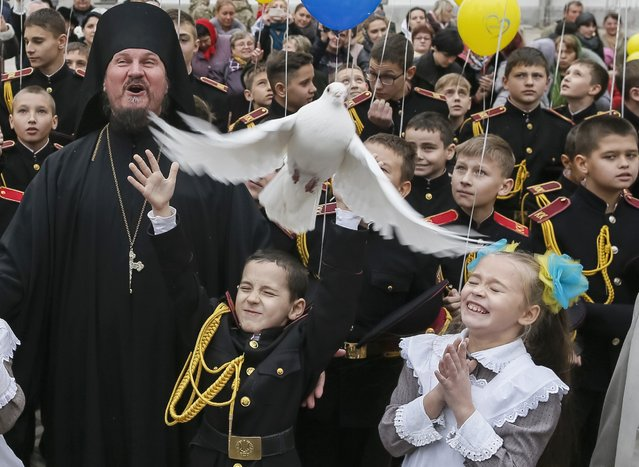 A young military cadet releases a pigeon after an oath-taking ceremony at the Kiev Pechersk Lavra monastery in Kiev, November 14, 2014. About 100 new young military cadets took part in an oath-taking ceremony on Friday, according to officials. (Photo by Gleb Garanich/Reuters)