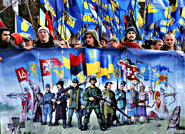 Activists of the of nationalist Svoboda (Freedom) party hold a poster and their flags during a  rally in Kiev, Ukraine, Wednesday October 14, 2015. Ukraine is marking the 'Defender of the Fatherland Day'. (Photo by Efrem Lukatsky/AP Photo)