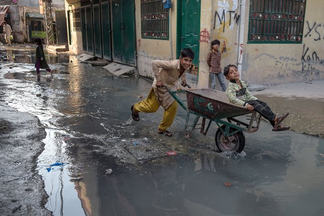 Children play in puddles of wastewater on a street in a slum area on the outskirts of Islamabad on September 9, 2020. (Photo by Farooq Naeem/AFP Photo)