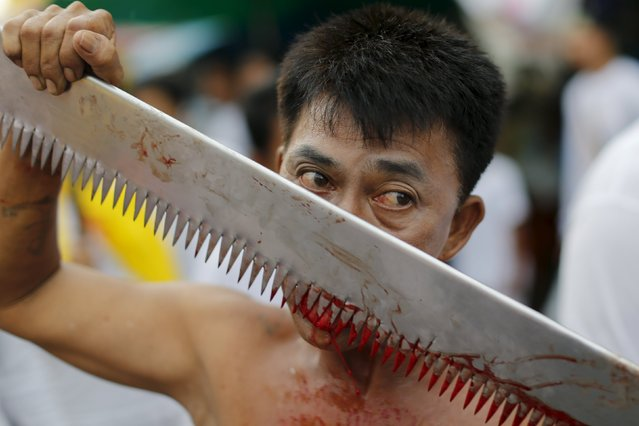 A devotee of the Chinese Bang Neow shrine cuts his tongue to make it bleed during a procession celebrating the annual vegetarian festival in Phuket, Thailand October 18, 2015. (Photo by Jorge Silva/Reuters)