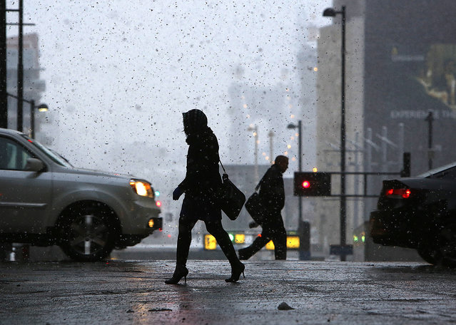 Pedestrians make their way through downtown Cincinnati, Monday morning, November 17, 2014, as the season's first snowfall resulted in thousands of power outages in the Cincinnati area. The National Weather Service reported accumulations of 2 to 4 inches of snow in northern and central Ohio by Monday morning, while the southwest section of the state got 3 to 5 inches. (Photo by Carrie Cochran/AP Photo/The Cincinnati Enquirer)