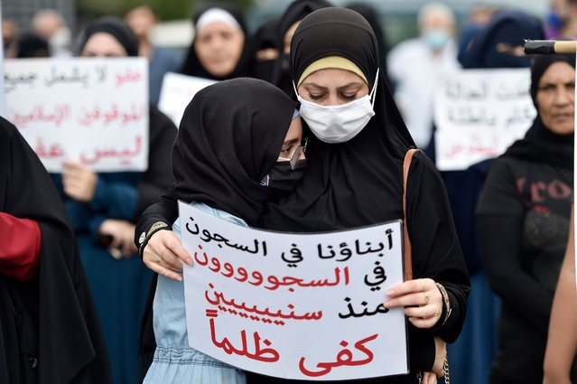 """A girl hugs her mother during a protest for relatives and families of Islamic prisoners at Roumieh prison as they carry placards calling for clemency for their relatives after the Friday prayers in the coastal town of Sidon, Lebanon, 25 September 2020. The protesters which included demonstrations in Sidon, Baalbeck and Tripoli, have been calling for clemency for their relatives, many of whom were arrested on suspicion of joining outlawed Islamist groups, taking up arms against the state or """"undermining the Army"""" """"without exception"""" and for the protection of prisoners following the spread of COVID-19 in the facility, where according to media reports, there is an increasing numbers of COVID-19 cases. (Photo by Wael Hamzeh/EPA/EFE/Rex Features/Shutterstock)"""