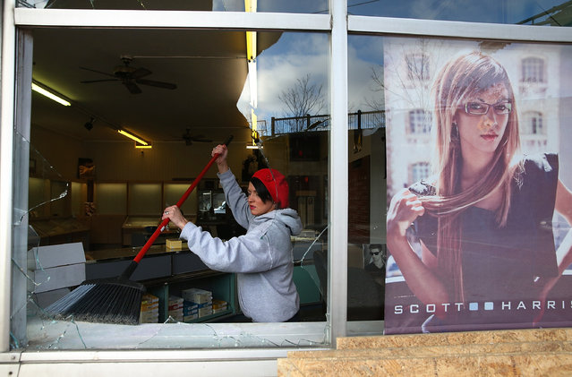 A worker cleans up glass at a business that was damaged during a demonstration on November 25, 2014 in Ferguson, Missouri. (Photo by Justin Sullivan/Getty Images)