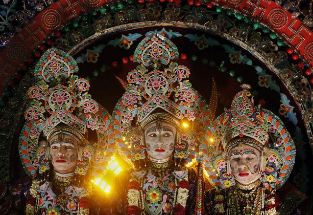 Indian artists dressed as Hindu deities Laxman, left, Rama, center, and Sita, sit in a tableau during a Dussehra festival procession in Allahabad, India, Friday, October 16, 2015. The festival celebrates the victory of good over evil. (Photo by Rajesh Kumar Singh/AP Photo)