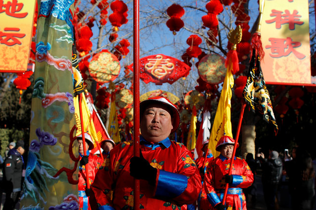 Performers take part in the re-enactment of a Qing Dynasty ceremony, in which emperors prayed for good harvest and fortune for the Chinese New Year, during the Spring Festival Temple Fair at the Temple of Earth in Ditan Park in Beijing, China, February 16, 2018. (Photo by Thomas Peter/Reuters)