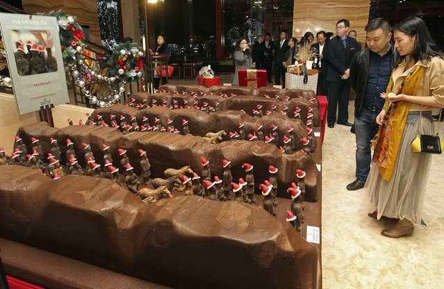 Customers look at miniature chocolate Terracotta Warriors wearing Santa Claus hats on display at the lobby of a hotel for the upcoming Christmas celebrations in Xi'an, Shaanxi province November 21, 2014. A total of 300 miniature replicas of Terracotta Warriors were made by ten pastry chefs in ten days from about 100 kilograms (220 lb) of chocolate. The hats were made of sweets, local media reported. (Photo by Reuters/China Daily)