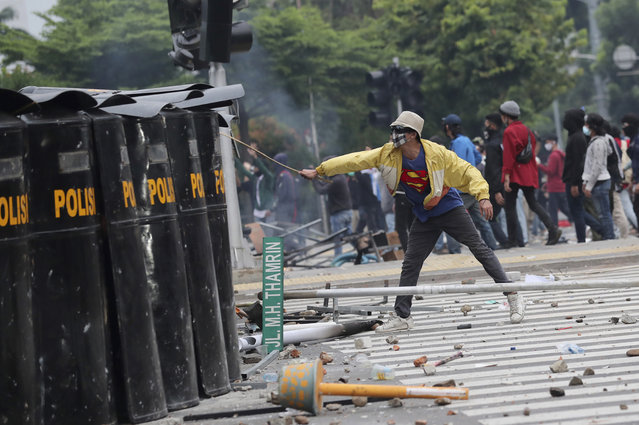 A protester taunts a line of police during clash in Jakarta, Indonesia, Thursday, October 8, 2020. (Photo by Tatan Syuflana/AP Photo)