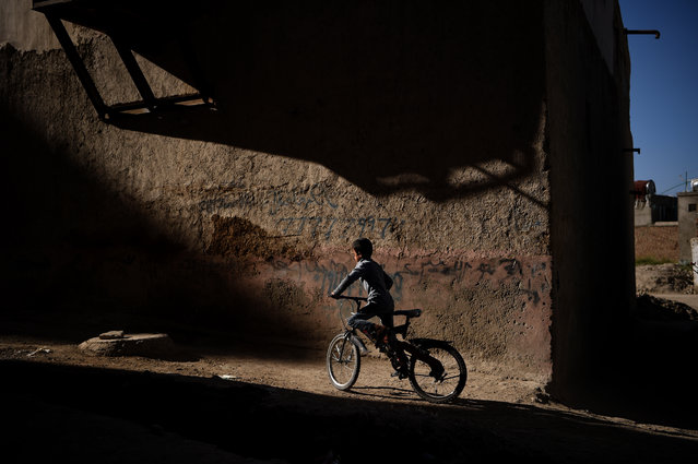 A child rides his bicycle on a road in the old part of Kabul on September 21, 2020. (Photo by Wakil Kohsar/AFP Photo)