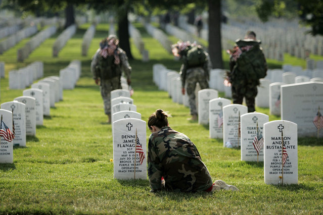 Kristin Kenney of Edison, New Jersey, sits at the grave of her boyfriend, Army Sgt. Dennis Flanagan, while Members of the 289th Military Police Honor Guard plant flags at grave sites at Arlington National Cemetery in Arlington, Virginia, on May 25, 2006. Flanagan died in Iraq on January 21, 2006. (Photo by Gerald Herbert/AP Photo/The Atlantic)