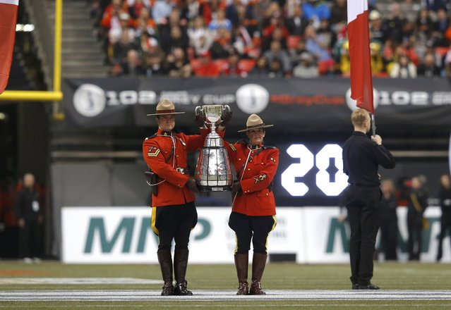 Royal Canadian Mounted Police officers hold the Grey Cup during ceremonies ahead of the start of the CFL's 102nd Grey Cup football championsionship between the Hamilton Tiger Cats and the Calgary Stampeders in Vancouver, British Columbia, November 30, 2014. (Photo by Todd Korol/Reuters)