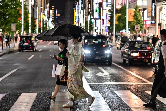 Pedestrians cross a street during a rainy evening in Tokyo on October 7, 2020. (Photo by Charly Triballeau/AFP Photo)