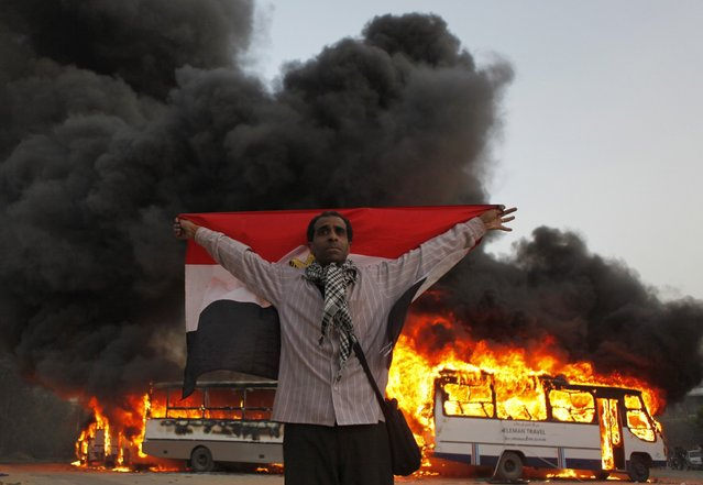 An anti-Mursi protester stands with the national flag after protesters burn Muslim Brotherhood buses during clashes near the Muslim Brotherhood's national headquarters in Cairo's Moqattam district March 22, 2013. (Photo by Reuters/Stringer)