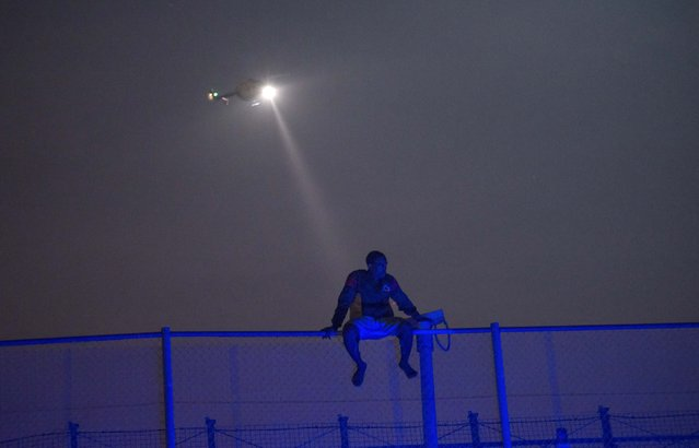 An African migrant sits on top of a border fence covered in razor wire between Morocco and Spain's north African enclave of Melilla, during a latest attempt to cross into Spanish territory, in this June 14, 2014 file photo. (Photo by Jesus Blasco de Avellaneda/Reuters)
