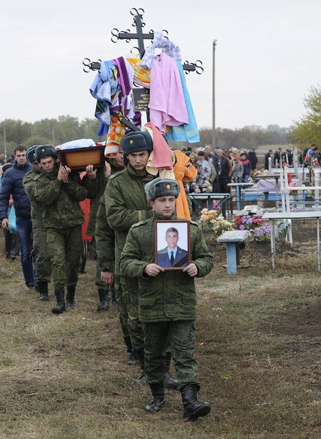Russian servicemen carry a portrait and a coffin of Vadim Kostenko, one of the Russian air force's support staff in Syria, during his funeral in the village of Grechnaya Balka, north-west of Krasnodar, Russia October 28, 2015. The body of the first Russian soldier to die in Syria was returned to his parents with wounds inconsistent with the official version that he hanged himself, the serviceman's uncle told a Russian newspaper on Wednesday. (Photo by Reuters/Stringer)