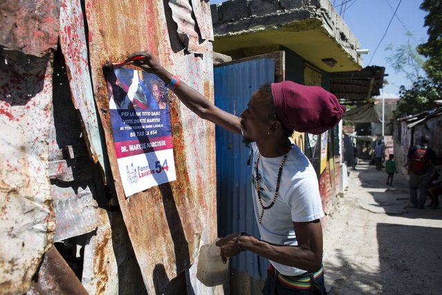 In this September 21, 2016 photo, a supporter of the Fanmi Lavalas political party pastes a campaign poster of Haiti's former President Jean Bertrand-Aristide with presidential candidate Maryse Narcisse before a campaign event in Port-au-Prince, Haiti. (Photo by Dieu Nalio Chery/AP Photo)
