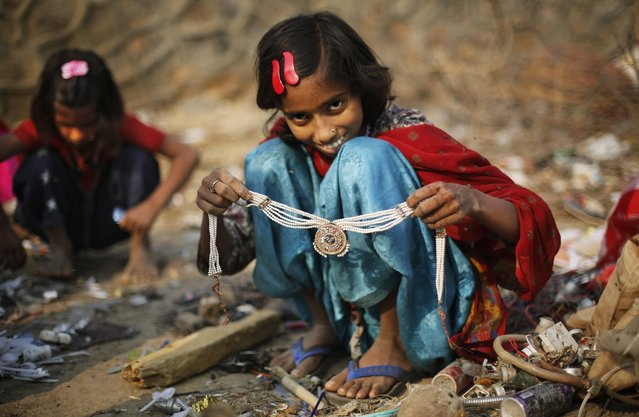 In this November 29, 2014 photo, Murshida, 12, shows a necklace found while segregating trash outside her rented shanty on the outskirts of New Delhi, India. Murshida lives with her mother, a rag picker, and spends the day along with her 7-year-old brother at a landfill picking through other people's garbage to find salvageable bits to resell or recycle. The children counted themselves lucky if they find a discarded toy or plastic jewelry to play with. (Photo by Altaf Qadri/AP Photo)