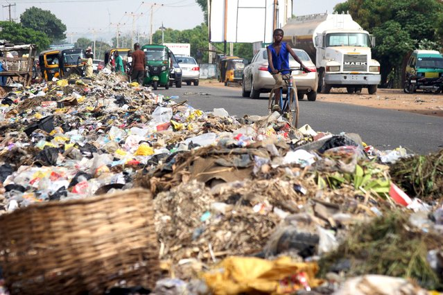 A boy rides a bicycle past a garbage dump on a major road in Kaduna, Nigeria October 29, 2015. (Photo by Reuters/Stringer)