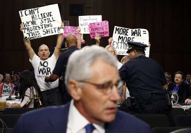 Anti-war protesters hold up signs as U.S. Secretary of Defense Chuck Hagel takes his seat to testify at the Senate Armed Services Committee hearing on the U.S. policy toward Iraq and Syria and the threat posed by the Islamic State, on Capitol Hill in Washington, in this September 16, 2014 file photo. (Photo by Kevin Lamarque/Reuters)