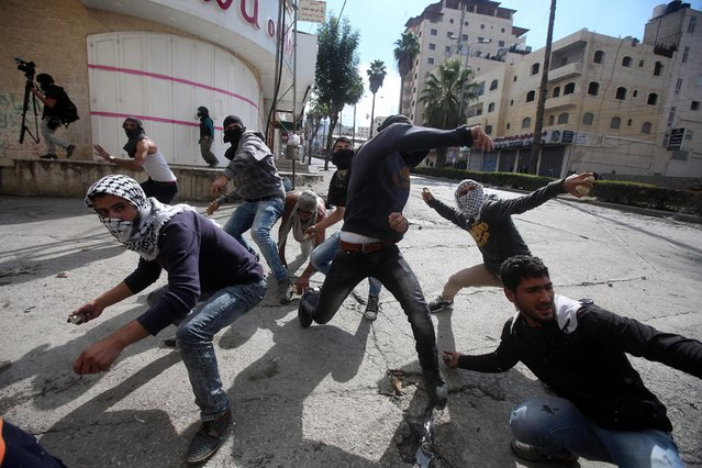 Palestinian protesters throw stones at Israeli soldiers during clashes in the West Bank of Hebron, 30 October 2015. Since the start of October, violence that has included stabbings as well as clashes between Palestinian protesters and Israeli security forces has killed at least 65 Palestinians and 10 Israelis. (Photo by Abed Al Hashlamoun/EPA)