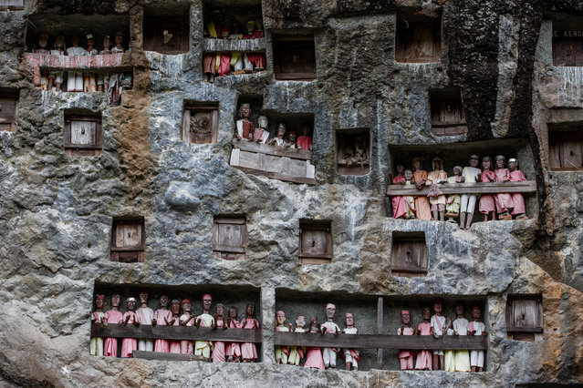 The Liang with Tau-Tau, or effigies made of wood in Lemo Toraja, South Sulawesi, Indonesia on August 14, 2016. These life-sized representations of the dead were once produced only for the wealthy. They are guardians of the tombs and protectors of the living. (Photo by Agung Parameswara/The Washington Post)