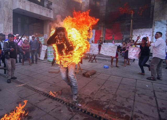 Farmer Agustin Gomez Perez is engulfed in flames after he was set on fire to protest the imprisonment of his father who is charged with murder, stealing cattle and organized crime in Tuxtla Gutierrez, Mexico, December 5, 2014. (Photo by Jacob Garcia/Cuartoscuro)