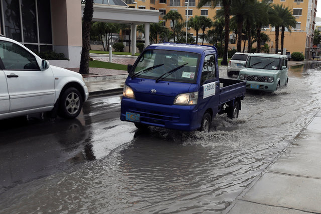 Cars drive though a flooded street due to early rains associated with Hurricane Matthew in Nassau, Bahamas October 5, 2016. (Photo by Carlos Garcia Rawlins/Reuters)