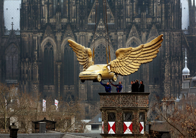 Workers install a golden winged car on the roof of the City Museum in Cologne, western Germany, on April 4, 2013. The car, a creation by German artist H. A. Schult, is brought back to the roof after its restauration at Ford. (Photo by Oliver Berg/AFP Photo)