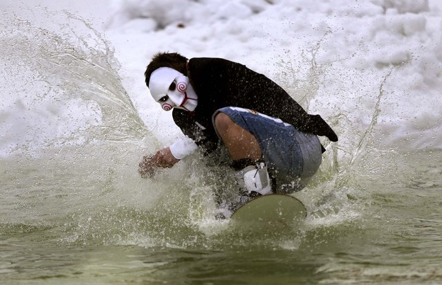 """A snowboarder takes part in the comic competition """"Californication 6.0"""" during celebrations of the end of winter in Silichi, Belarus, on April 6, 2013. (Photo by Sergei Grits/Associated Press)"""