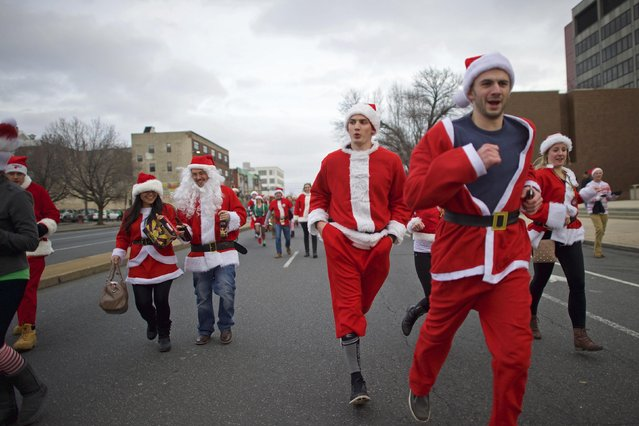 "People in Santa Claus outfits participate in the ""Running of the Santas"" in Philadelphia, Pennsylvania December 13, 2014. The annual pub crawl event began in 1998. (Photo by Mark Makela/Reuters)"