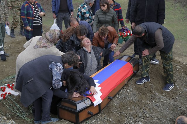 Relatives of Mkhitar Beglarian, an ethnic Armenian soldier of Nagorno-Karabakh army who was killed during a military conflict, mourn during his funeral at a cemetery in Stepanakert, the separatist region of Nagorno-Karabakh, on Sunday, November 15, 2020. Ethnic Armenian forces had controlled Nagorno-Karabakh and sizeable adjacent territories since the 1994 end of a separatist war. Fighting resumed in late September and have now ended with an agreement that calls for Azerbaijan to regain control of the outlying territories as well as allowing it to hold on to parts of Nagorno-Karabakh that it seized during the fighting. (Photo by Sergei Grits/AP Photo)