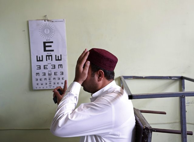 An Afghan man takes an eye test before receiving a driving license at a traffic police department in Kabul August 23, 2014. (Photo by Mohammad Ismail/Reuters)