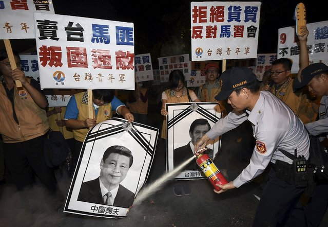 A police officer puts out fire on the portraits of Chinese President Xi Jinping and Taiwan's President Ma Ying-jeou (R) during a protest against the upcoming Singapore meeting between Ma and Xi, outside Taipei Songshan airport, November 7, 2015. Leaders of political rivals Taiwan and China meet for the first time in more than 60 years on Saturday for talks that come amid rising anti-Chinese sentiment on the self-ruled democratic island and weeks ahead of elections. (Photo by Reuters/Stringer)