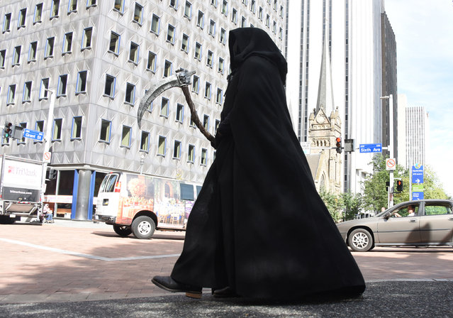 """In an October 10, 2016 photo, the """"Grim Reaper"""" is on the march for distracted pedestrians in Pittsburgh, Pa. The Pittsburgh Downtown Partnership and other groups are trying to """"scare"""" pedestrians off their cellphones by having actors dressed as the Grim Reaper and zombies urging people to look up from their cellphones while they're walking downtown. (Photo by Darrell Sapp/Pittsburgh Post-Gazette via AP Photo)"""