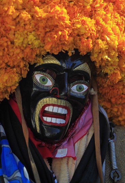 "A traditional Mexican masked dancer called ""Tlacololeros"" performs during the ""Paseo del Pendon"", a traditional artistic march in Chilpancingo, December 21, 2014. (Photo by Jorge Dan Lopez/Reuters)"