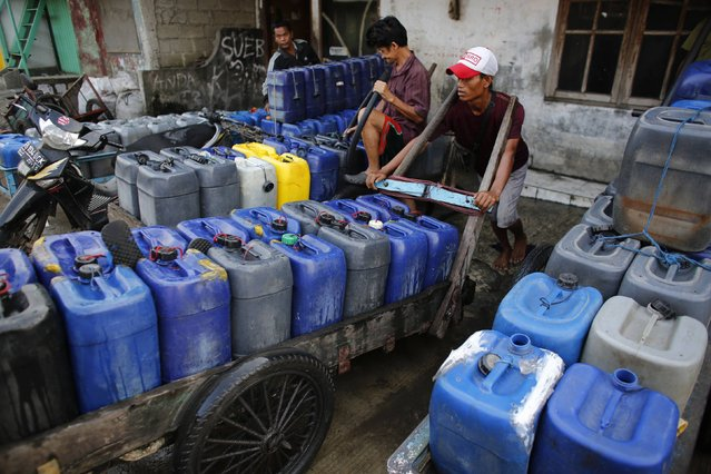 Delivery men fill up plastic jerry cans with water before setting off to deliver them to residents who increasingly have no access to piped or well water in Pluit, north Jakarta, September 30, 2014. (Photo by Darren Whiteside/Reuters)
