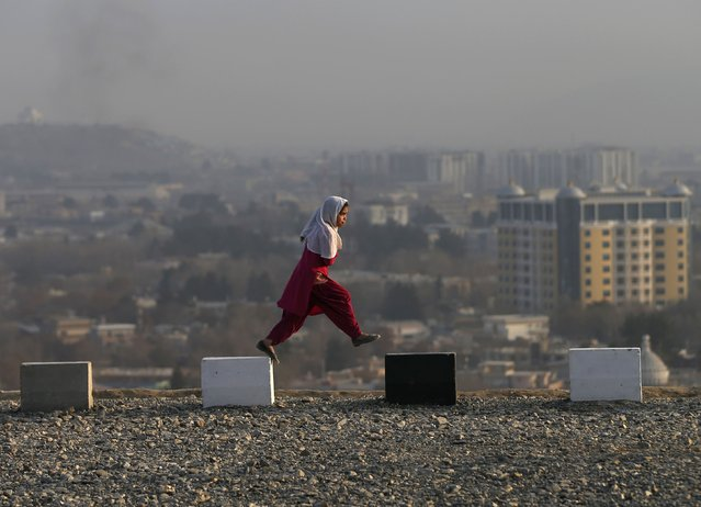 An Afghan girl walks on a hilltop overlooking Kabul December 21, 2014. (Photo by Mohammad Ismail/Reuters)