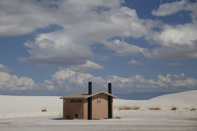 A toilet block is surrounded by white sand in the White Sands National Monument park area near Alamogordo, New Mexico, United States, October 6, 2015. The park's white sand dunes are composed of gypsum crystals. It is the largest gypsum dune field in the world. (Photo by Shannon Stapleton/Reuters)