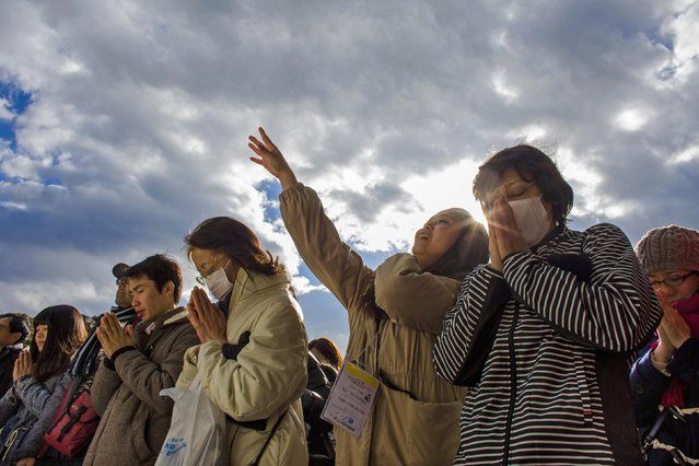 People pray and throw offerings for the new year at the Shinto Meiji Shrine in Tokyo January 1, 2015. (Photo by Thomas Peter/Reuters)