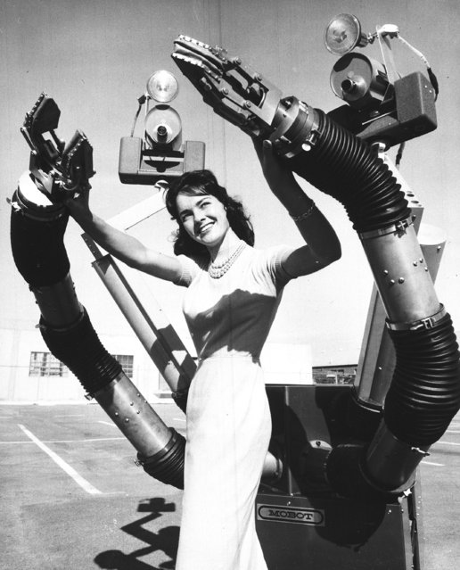"The tentacle-like arms of ""Mobot Mark II"", a mobile robot built by Hughes Aircraft Company of Culver City, Calif., close in on Colleen Adams as it demonstrates its almost human actions on December 13, 1960. The robot was designed to perform tasks in areas too dangerous for humans. The six foot arms are double-jointed at shoulder, elbow and wrist, and television camera ""eyes"" transmit images of the robot's performance to a human operator at a remote control console. (Photo by AP Photo)"