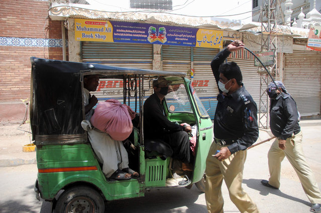 Police officers restrict a rickshaw driver defying the nation-wide lockdown to curb the spread of the coronavirus in Hyderabad, Pakistan, Friday, March, 3, 2020. Some mosques were allowed to remain open in Pakistan on Friday, the Muslim sabbath when adherents gather for weekly prayers, even as the coronavirus pandemic spread and much of the country had shut down. (Photo by Pervez Masih/AP Photo)